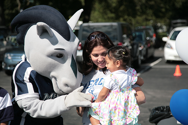 Mav Mascot with Mercy student and young child